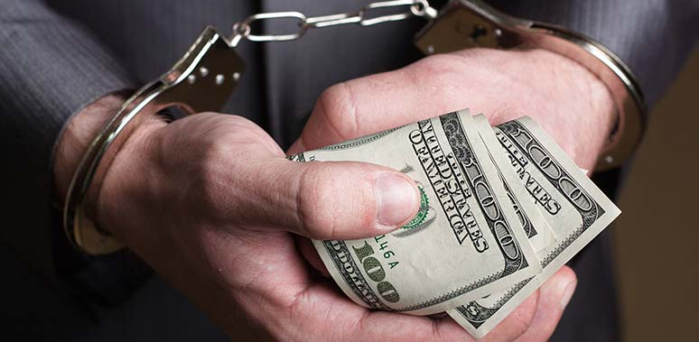 Man Holding Rolled $100 Bills in Handcuffs Feature