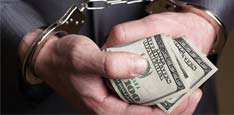 Man Holding Rolled $100 Bills in Handcuffs Thumbnail